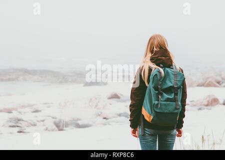 Woman backpacker standing alone outdoor Travel Lifestyle and melancholy emotions concept foggy nature on background - Stock Photo