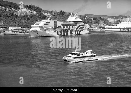 Barcelona, Spain - March 30, 2016: big and small ships or boats marine vessels enter port on blue sea water along beautiful green coast on natural background - Stock Photo