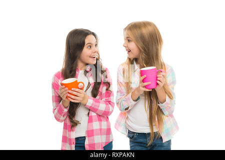 Hot cocoa recipe. Make sure kids drink enough water. Girls kids hold cups white background. Sisters hold mugs. Drinking tea juice cocoa. Relaxing with drink. Children drink enough during school day. - Stock Photo