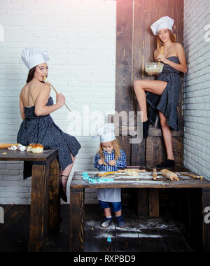Toddler boy and girls in chef hats in kitchen - Stock Photo