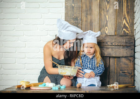 Sad child boy with woman in kitchen - Stock Photo