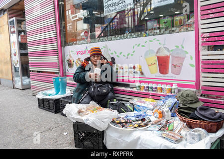 A street scene in Jackson Heights Queens, New York featuring a women selling knick knacks & clothing while talking on her cell phone. On 82nd Street. - Stock Photo