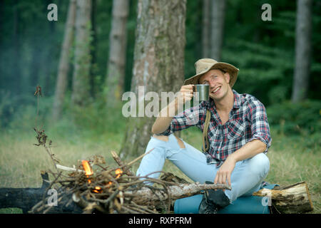 Guy in hat sits near bonfire , trees on background, defocused. - Stock Photo