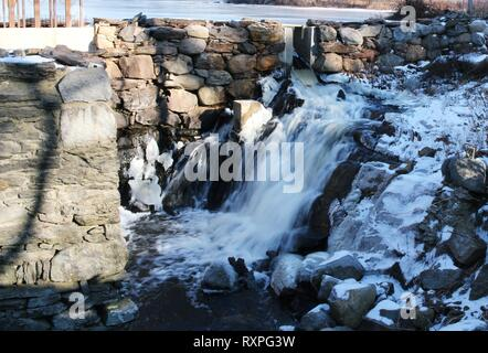 Cascading waterfalls flowing down icy rocks in Palermo, Maine, USA - Stock Photo