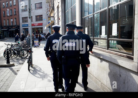 three garda officers one female two male on foot patrol in the temple bar area of Dublin Republic of Ireland europe - Stock Photo