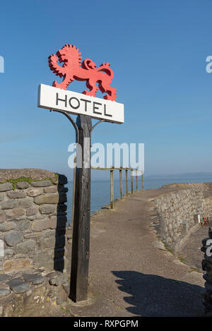 Clovelly, Devon, England, UK, March 2019. red hotel sign mounted on an old oak post on the seafront in Clovelly. - Stock Photo