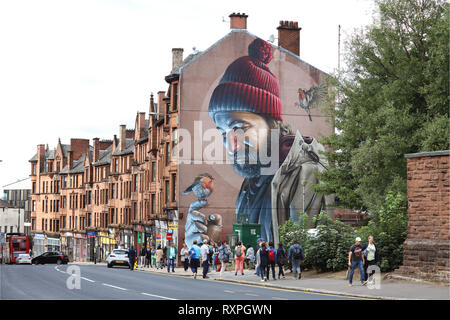 Mural on High St. by street artist Sam Bates, aka Smug, depicting St. Mungo the patron saint and founder of the City of Glasgow, Scotland - Stock Photo