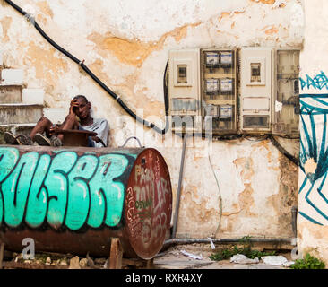 Havana, Cuba - 25 July 2018: A Cuban man sitting on steps with his legs on an oil tank leaning against a building in the shade avoiding the heat. - Stock Photo