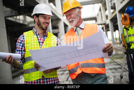 Engineer, foreman and worker discussing in building construction site - Stock Photo