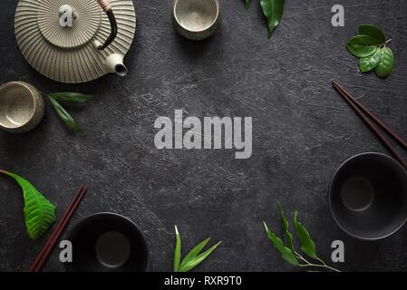 Asian food background - tea set, bowls and chopsticks on black background. Asian menu design, chinese japanese cuisine concept. - Stock Photo