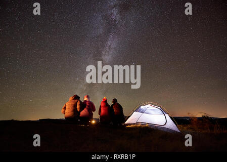 Summer camping in the mountains. Back view of happy friends hikers having a rest together around campfire near glowing tourist tent at night. On backg - Stock Photo