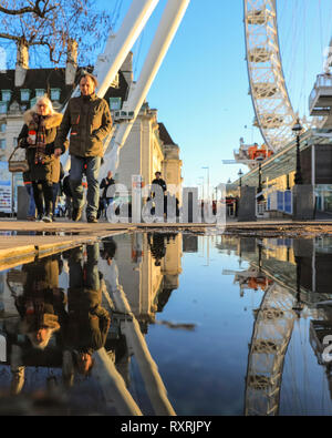 South Bank, London, UK. 10th Mar 2019. People walk in the late afternoon sunshine on London's South Bank. Following a day of sunshine and rain, the late afternoon sees a return of warm evening sunlight with lots of puddles and reflections near the London Eye. Credit: Imageplotter/Alamy Live News - Stock Photo