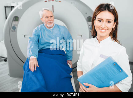 Doctor radiologist, smiling while looking at camera. Behind her sitting senior patient. CT scanner in hospital - Stock Photo