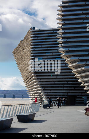 The cliff shape design of the V&A Museum jutting out over the River Tay in Dundee with the Tay railway bridge in the background. - Stock Photo