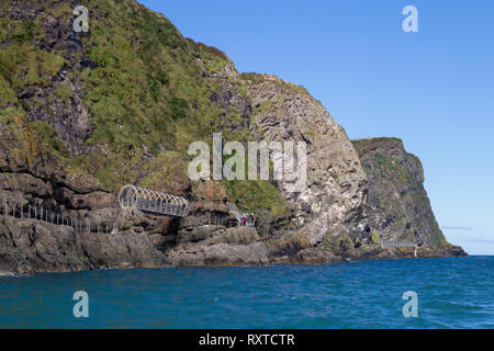 People walking along The Gobbins Cliff Path on Belfast Lough in County Antrim, Northern Ireland. - Stock Photo