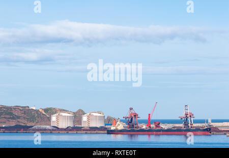 Coal cargo ship moored in port with lifting cargo cranes, ships and grain. Gijón, Asturias, Spain. - Stock Photo