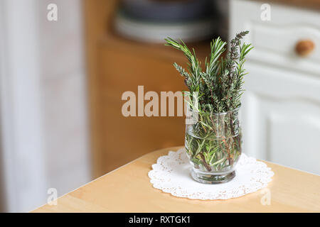 Fresh thyme and fresh rosemary in transparent glass. Mixed cut herbs on the kitchen table. Interior of the kitchen, decoration. White napkin. - Stock Photo
