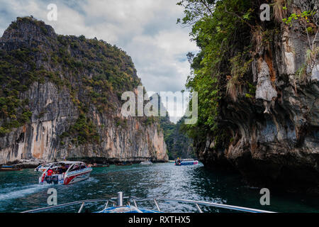 Tourist cruise boats are moving through the passage between the Phi Phi Islands, Thailand - Stock Photo