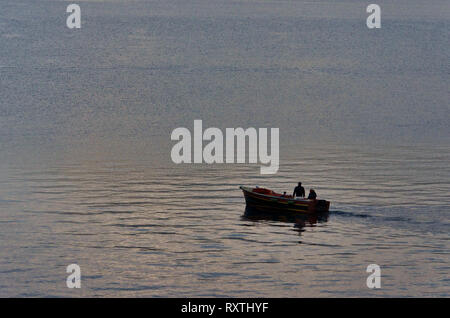 Little boat with two fishermen on the lake at down, light reflection on the water, rough water surface, tranquil scene from Lake Iseo in Italy - Stock Photo