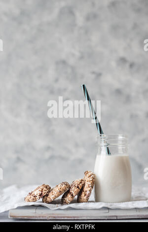 Stack of freshly baked tahini chocolate chip cookies with a bottle of milk