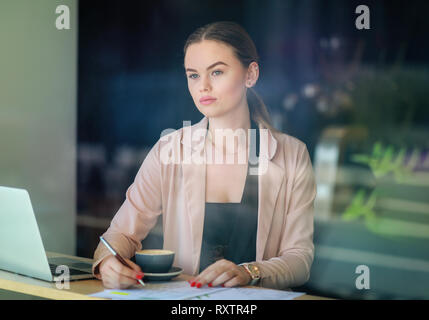 Elegant business woman looking through the window in a cafe shop. Thoughtful Look. Selective focus and reflexion on window - Stock Photo