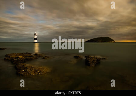Penmon Lighthouse (Trwyn Du Lighthouse) and Puffin Island at night, Anglesey UK - Stock Photo