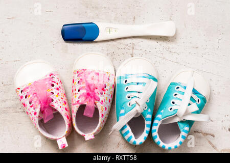 Baby booties pink and blue on a light background next to a positive pregnancy test. Ivf pregnancy concept - Stock Photo