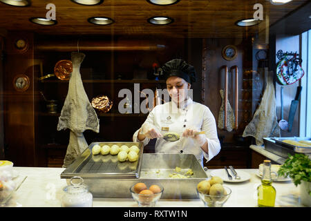 A cook is seen preparing traditional cod fish cakes in a traditional snack bar in the old town. In 2018, Porto entered the list of the 100 most visited cities in the world in a ranking prepared by Euromonitor International. In 2018 it is estimated that the number of tourists reached 2.39 million. - Stock Photo