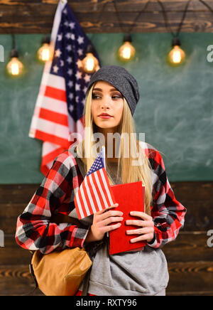 College students in library against composite image of USA national flag. English female student with the American flag at the background. - Stock Photo