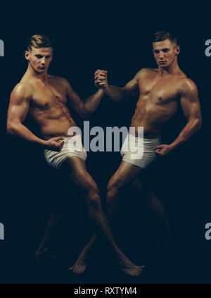 Sport workout for bodybuilder. Fitness dieting and flexibility in acrobatics. Circus gymnasts at pilates or yoga training. Twins men with muscular - Stock Photo