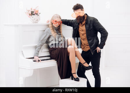 Blond girl sitting on white piano while bearded man in leather jacket standing next to her. Couple in enormous orange glasses posing in white studio - Stock Photo