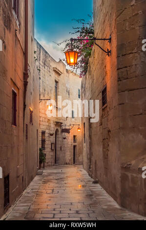 Mdina, Malta: narrow street paved with setts in medieval town with limestone walls and lantern lights in the early evening - Stock Photo