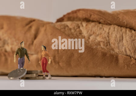 A miniature woman and man figure standing next to big baguette bread and counting coins. Shallow depth of field. Family budget, healthy lives - Stock Photo