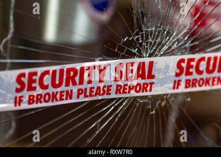 Police Security Seal tape across the broken glass window - Stock Photo