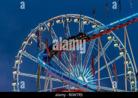 Amusement park at night - Ferris wheel and roller coaster in motion - Stock Photo
