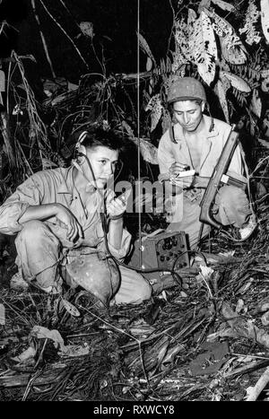Navajo code-talkers Corporal Henry Bake, Jr., (left) and Private First Class George H. Kirk (right), serving with a Marine Signal Unit, operate a portable radio set in a clearing they've just hacked in the dense jungle close behind the front lines on Bougainville Island in Papua New Guinea during World War II in December 1943. - Stock Photo