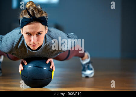 Fit and muscular woman with piercing eyes doing intense core workout with kettlebell in gym. Female exercising at crossfit gym. - Stock Photo