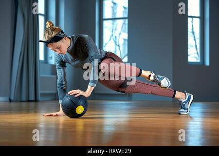 muscular woman doing intense core workout in gym strong
