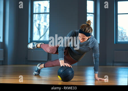 Fit and muscular woman doing intense core workout with kettlebell in gym. Female exercising at crossfit gym. - Stock Photo