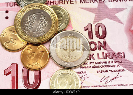 A macro image of an assortment Turkish coins close up on a green, twenty Turkish lira bank note - Stock Photo
