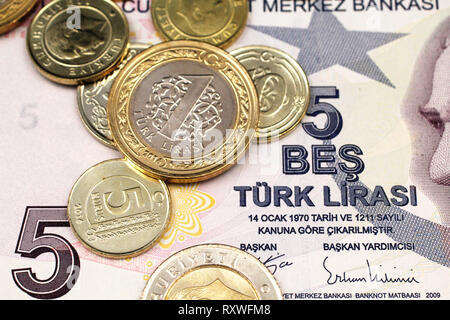 A macro image of an assortment Turkish coins close up on a purple, five Turkish lira bank note - Stock Photo