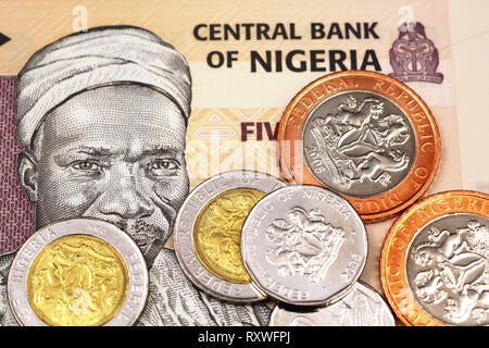 A macro image of miscellaneous Nigerain coins on a five Naira bank note from Nigeria - Stock Photo