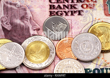 A close up image of assorted coins from Egypt on the background of an Egyptian ten pound bank note - Stock Photo