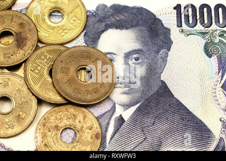 A close up image of Japanese five yen coin on a thousand yen bank note in macro. - Stock Photo