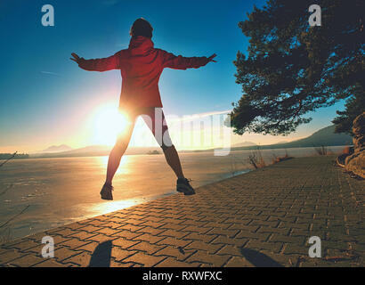 Sports girl runs through the morning park by the lake - Stock Photo