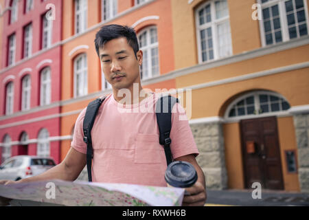 Young Asian man reading a map while exploring the city - Stock Photo