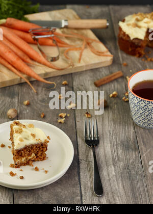 A slice of carrot cake pictured with a cup of tea - Stock Photo