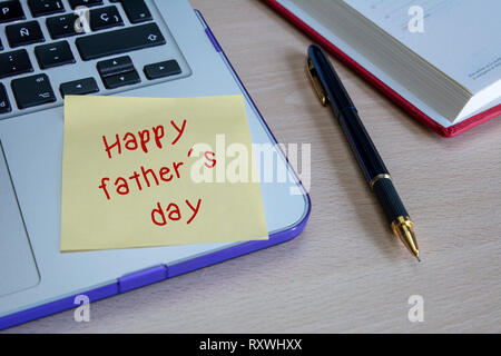 Laptop and stick note with happy fathers day written on wooden table - Stock Photo