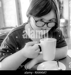 Young girl with Downs Syndrome having afternoon tea at White Mill Mariana, Northamptonshire. - Stock Photo