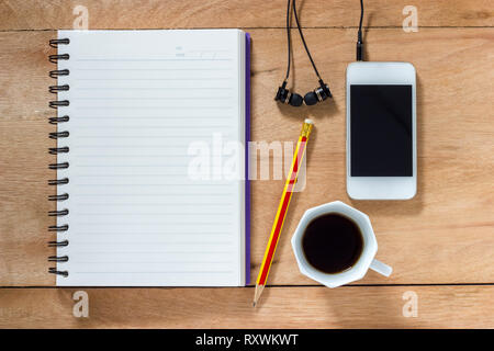 Bank notebook with pencil laying on the brown table. White mobile with earphones and black coffee put on the table as well. - Stock Photo
